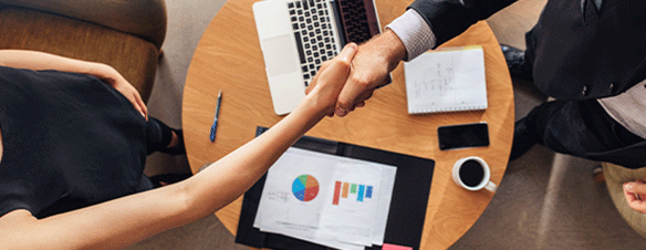Man and woman shaking hands over a table with graphs, successful R&D Tax Credits claim approved