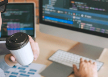 R&D Tax Credits man coding while holding a cup of takeaway coffee