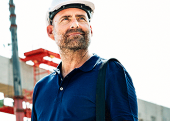 Man in a white safety hat smiling on a construction site, an eligible R&D sector