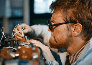 Man in glasses working on his R&D prototype