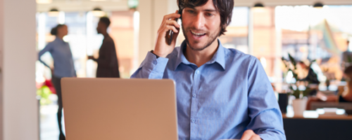 Happy consultant on the phone looking at his laptop discussing a R&D Tax Credits claim